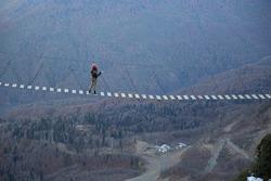 A girl in a hard hat walks on a bridge over a precipice