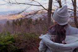 A girl in a hat and jacket stands on a panorama in the forest, the sky is a tree. Tourism and travel concept. Copy space