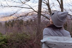 A girl in a hat and jacket stands on a panorama overlooking the hills and the village. Tourism and travel concept. Copy space.