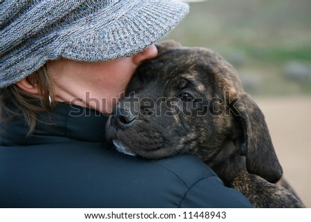 a girl in a hat holding a baby mastiff puppy