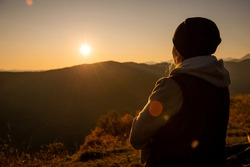 A girl in a hat looks at a beautiful fiery dawn in the mountains. Dawn cloudless sky overlooking Elbrus.