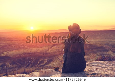 A girl in a hat on top of a hill in silence and loneliness admires a tranquil natural landscape in search of a soul. #1173726646