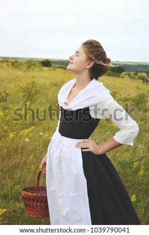 A girl in a historical costume with a basket standing in the field of yellow flowers. 18th century costume of a peasant girl