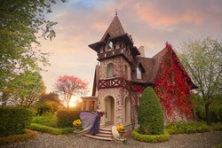 A girl in a lilac dress standing at the door of a beautiful art Nouveau cottage in the autumn garden. Romantic sunset photo.