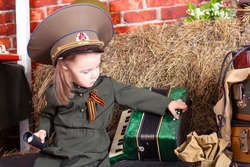 A girl in a military uniform holds an accordion in his hands. Victory Day. 9th May. A Great Victory.