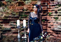 A girl in a mystical dark image in a black dress with flowers in her hair against the background of an old brick wall. Candles, black magic, Gothic beauty, mystical image. Halloween, black widow