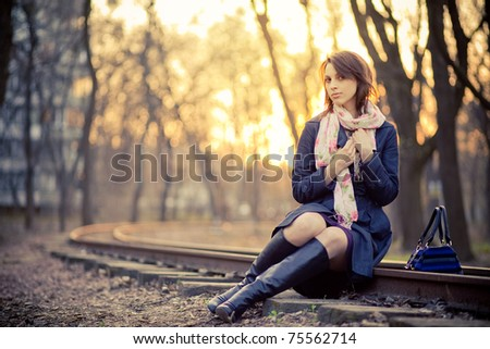 A girl in a park near the railway at sunset
