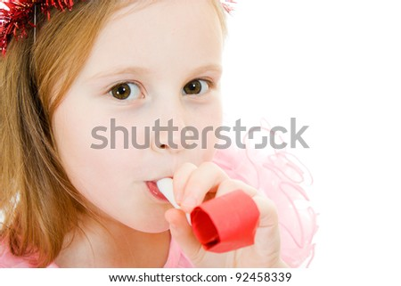 A girl in a pink dress and hat blowing in the pipe on a white background.