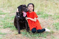 A girl in a red shirt was walking the lawn with a big black dog.