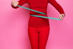 a girl in a red sweater and red pants measures her waist with a centimeter tape measure. the figure of a girl with a centimeter measuring the girl's waist