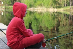 A girl in a red tracksuit is fishing in a forest lake sitting on a wooden bridge on a sunny spring day. Portrait of blond teenage girl in red outdoors in nature. Copy space.