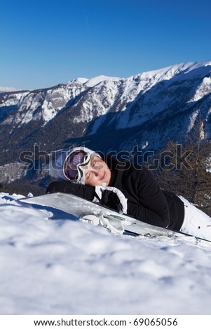 A girl in a ski suit in the mountains in winter laying on snowboard