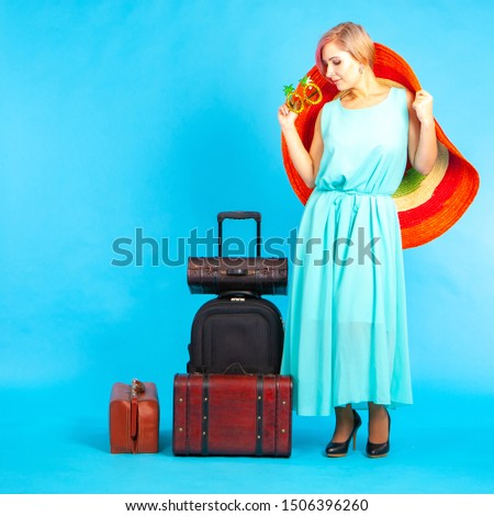 A girl in a straw hat and unusual glasses. Suitcases for travel. Sea tour. Dreams of summer vacation. Vacation planning. Sale of goods for recreation. Place for inscription. #1506396260