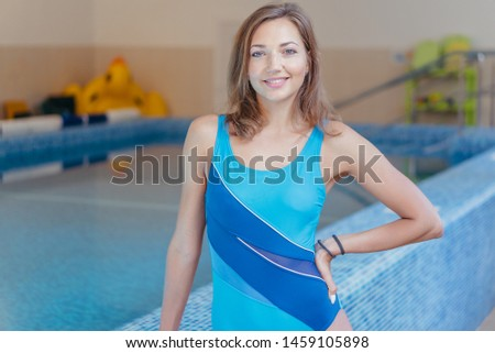 A girl in a swimsuit against the backdrop of the pool #1459105898
