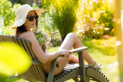 A girl in a swimsuit sitting in a deck chair with a refreshing mojito, sunbathes and enjoys the fresh air on a sunny day. The concept of summer holidays in 2020 is due to the spread of COVID-19.