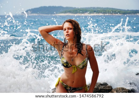A girl in a swimsuit with metal rings and wet hair stands on the background of the sea. Behind the spray from the walls, which are broken on a rocky shore. Summer Holidays in Croatia #1474586792