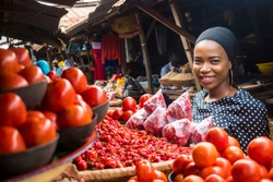 a girl in a typical african local market, at a stand where they sell tomatoes and pepper