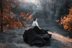 A girl in a vintage dress is running and looking around. The train waving in the wind. Art Photography. Landscape forest, orange trees. Gothic beauty, the dark queen. Wallpaper
