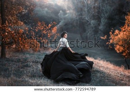 A girl in a vintage dress is running and looking around. The train waving in the wind. Artistic Photography