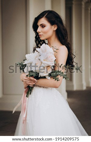 A girl in a wavy white wedding dress with a large bouquet of roses. The bride has long twisted hair Foto stock ©