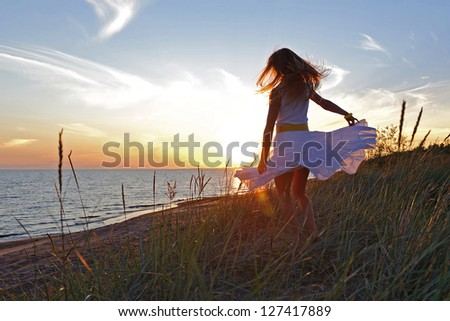 A girl in a white dress dancing on the beach