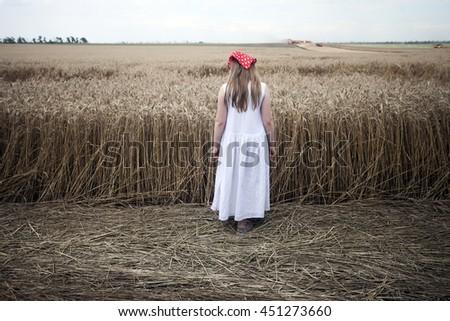A girl in a white dress near a wheat field . #451273660