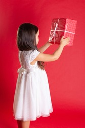 a girl in a white dress stands sideways and holds a red gift box, isolated on a vibrance background.