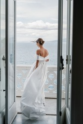A girl in a white satin wedding dress with gathered hair stands on an open terrace against the backdrop of mountains and the sea. A wedding dress with bare shoulders. Bride hair develops in the wind