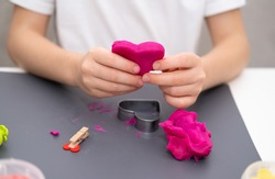 A girl in a white T-shirt sculpts a pink heart from plasticine. Valentine's Day, Mother's Day, Father's Day.