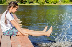 A girl in a white T-shirt sits by the lake on wooden walkways and splashes her bare feet in the water.