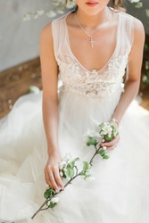 A girl in a white wedding dress holds in her hands a flowering branch of an apple tree. Hands of the bride close-up. On the neck of the girl a chain with a cross. Scarlet lips. Tulle wedding dress