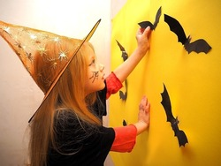 A girl in a witch costume decorates the room for Halloween. Child girl dressed as a witch on the background of bats. Preparing for Halloween. Halloween costume.