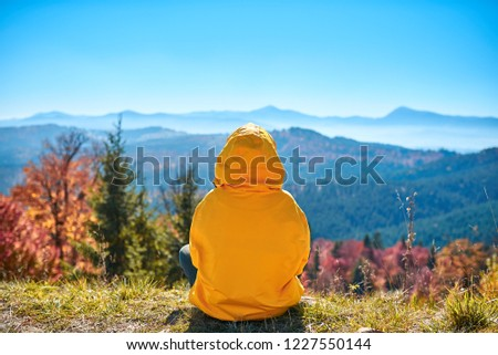 A girl in a yellow jacket admiring the autumn landscape on top of a mountain