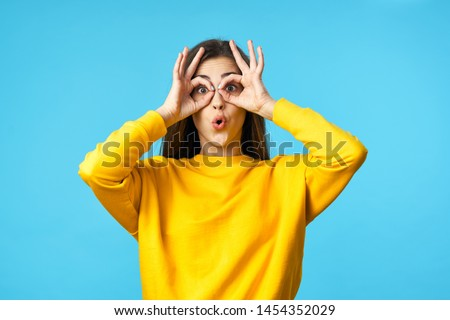 A girl in a yellow sweater on a blue background holding joined fingers in front of her face and narrowed her lips