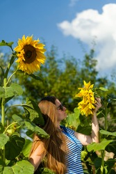 A girl in black glasses stands in tall sunflowers and holds on to them, a clear sunny day