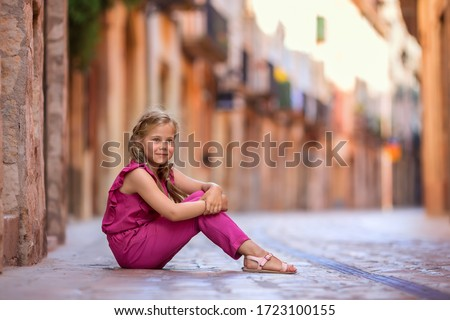 Photo of A girl in bright clothes is sitting on a paving slab against the background of a European city. An image with selective focus.