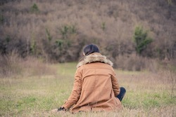 A  girl in brown parka sitting Indian style in the meadow, turned her back