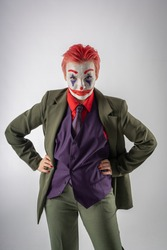 A girl in clown makeup (white face, red smile to the ears and blue diamonds on the eyes), with red hair, in a green jacket, red shirt, green trousers, purple vest and tie. The evil clown. On a white