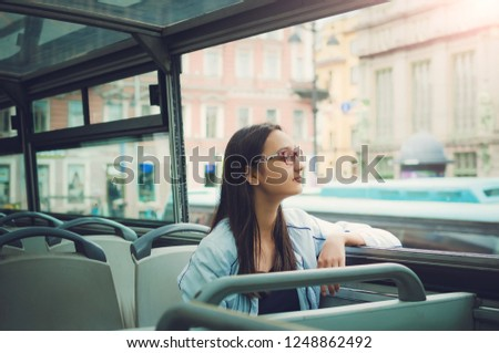 A girl in glasses with long dark hair sits inside a tour bus and looks into the camera and looks out the window. #1248862492