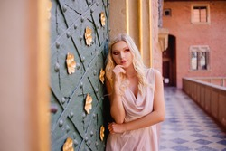 A girl in long dress in the castle. Blonde model posing, woman with long legs. Summer on vacation in a historic city
