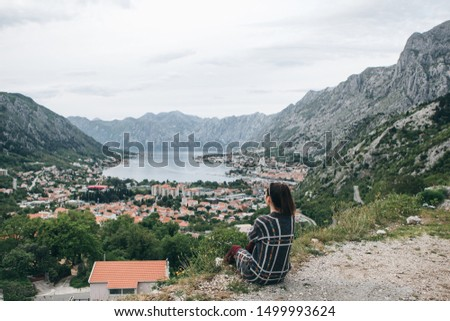 A girl in solitude sits on top of a hill or mountain and looks at a beautiful view of Kotor Bay in Montenegro. #1499993624