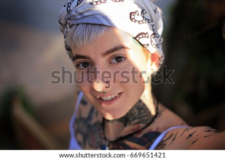 Stock Photo A girl in tattoos and with a piercing in her nose. She smiles. She has a white fringe and a shawl with horseshoes on her head. She has a blue stone on her neck. Sun ray on the face.