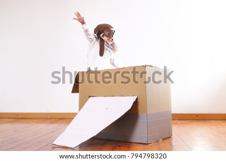A girl in the bedroom dressed as an airman or a pilot pretends to drive a paper airplane and imagines she is flying free in the sky. Concept of: freedom, success, dreams and play.