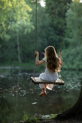 A girl in the forest swinging on a swing. Rope swing on a forest lake. Barefoot girl in a white dress with long hair. Image with selective focus.