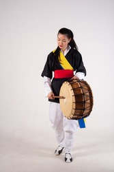 A girl in the national costume of Korea. Traditional musical instrument drum