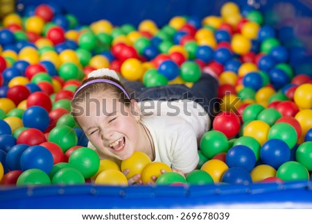 A girl in the playing room with many little colored balls. Close portrait