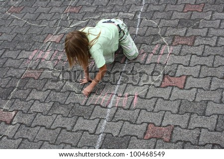 a girl in the street painting with chalk