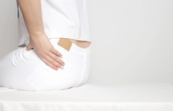 A girl in white clothes holds by the hip in which pain and inflammation. Femur Osteoarthritis Concept, copy space