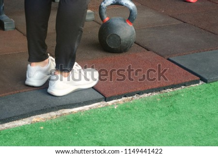 a girl in white sneakers and a metal dumbbell for classes on the backdrop of a gym where they practice fitness, sports and recreation  #1149441422