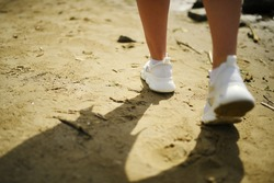 A girl in white sneakers is walking on the sand. Step forward. Shadow in the sand. Female legs on the beach background